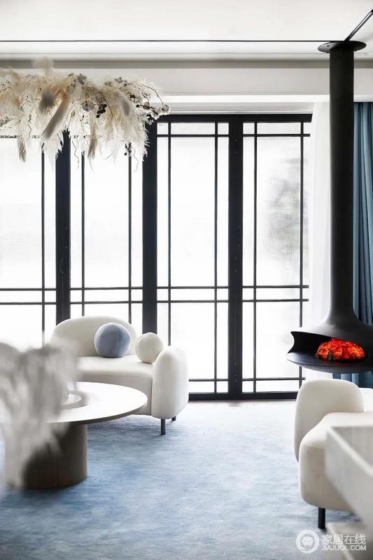 客厅空间设置吊挂壁炉,不仅让空间更加生动富有层次,也体现出满满的生活仪式感,温馨而有格调;白色沙发简约的设计与整个现代法式的空间相得益彰,满是雅致。