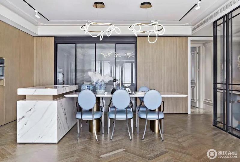 餐厅开放式的格局十分开阔,玻璃落地门解决了分区之余,让厨房空间更为通透;雅士白岛台、原木饰面餐桌、清新蓝法式餐椅组合出法式高雅;金色框架线性灯饰随性的设计,简约实用又不失创造力,令空间愈发时髦。