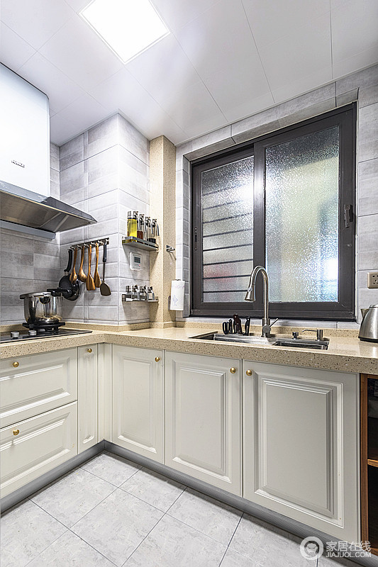 厨房选择米色调柜体和浅灰色墙砖搭配,色彩变化之中,让空间更为利落;采光让空间颇为明朗,也加强空间的通风。