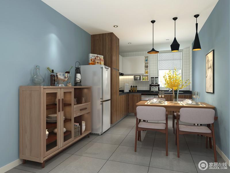餐厅以蓝色漆粉刷空间,营造了一个沉静而静谧的氛围,虽然开放式厨房的设计让空间具有强大的互动性,设计师利用褐色橱柜增加功能性;实木家具搭配工业风地黄铜吊灯,让生活温情之余,多了硬朗之美。