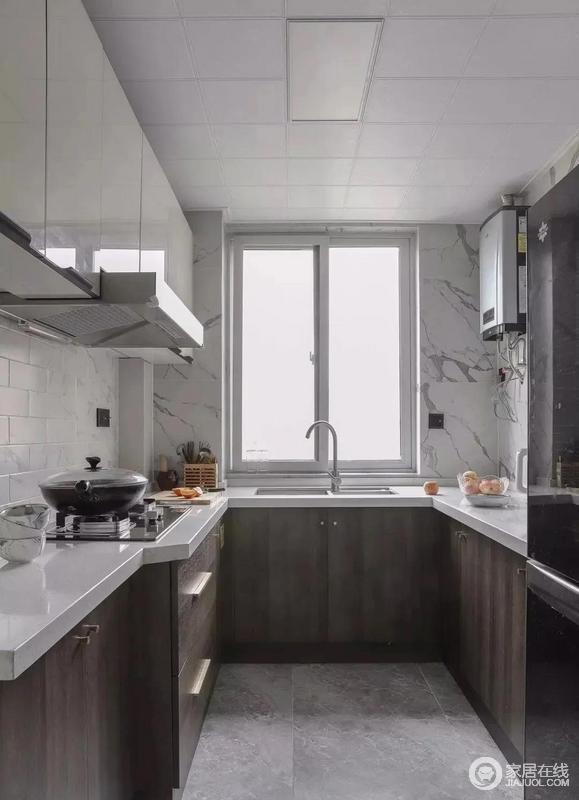 厨房的墙面用白砖和白色灰纹砖石来铺贴出简单的天然质感,而深灰色地砖奠定了空间的沉静;橱柜同样做分色处理,下柜选用深色木纹饰面板点缀金色把手,吊柜选用白色亮面亚克力材质柜门,黑色把手与门框镶嵌一体,更加便于平日的清洁打理,打造出简洁和利落的厨房。