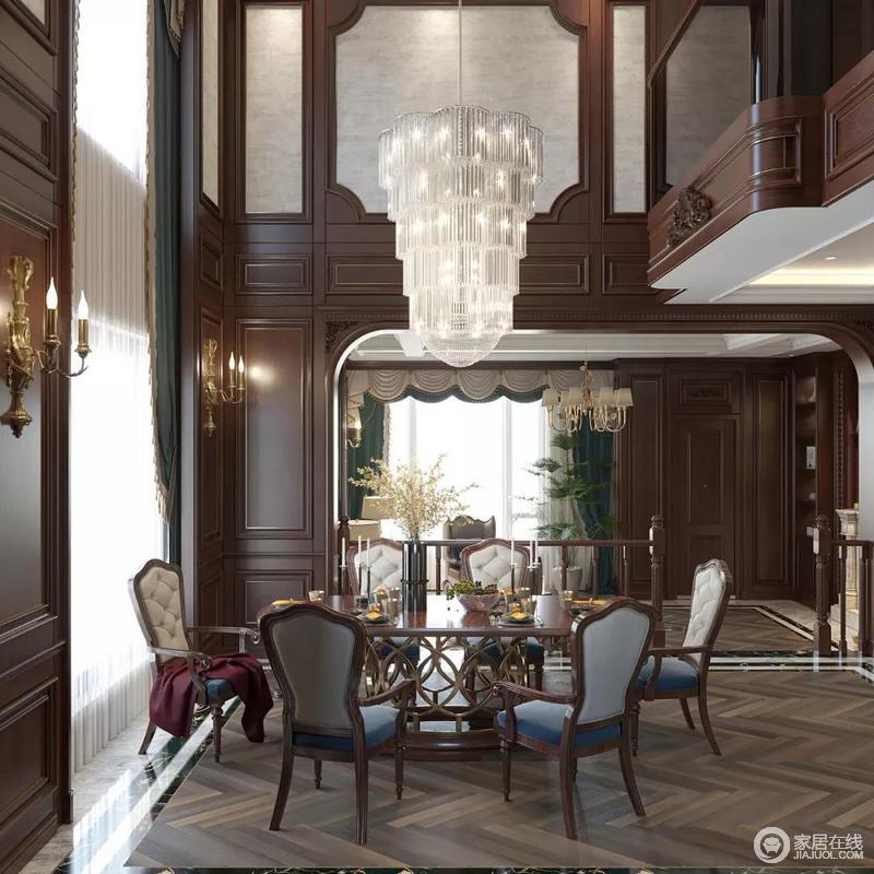 餐厅区因为别墅挑高,显得大气,再加上水晶灯的调和,充满艺术氛围和奢华气息;整个空间以褐色板材作装饰面,与波线地板,让空间动静相宜,美式风的餐桌餐椅,让人体会到空间的张力,也能瞬间捕捉到家的热闹和温馨。