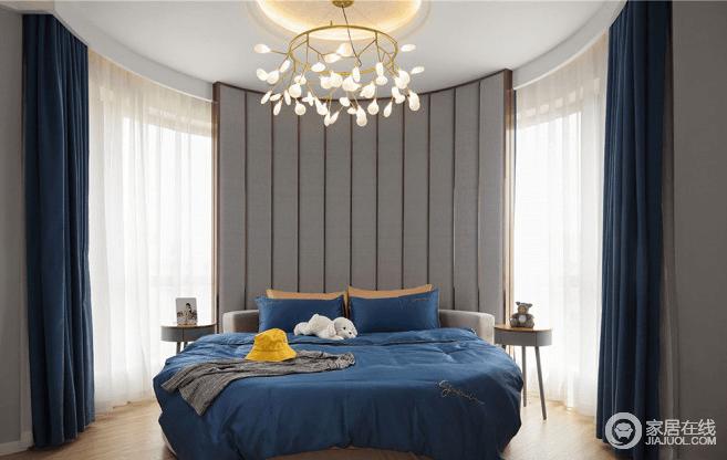 主卧室由于是圆形房间,里面有一整片弧形落地玻璃窗,在设计时如果按照常规的家具摆放,那就显得空间很小,很多功能是没有办法放置的,我们在设计时,就利用弧形的窗户造型,在落地窗户前面做了一面弧形的软包墙面做床背,放上圆形的床具,顶面上是圆弧形吊顶,在造型上能互相呼应、协调,这样设计后,不但让空间有了层次感,也让整个卧室空间变得更大了。