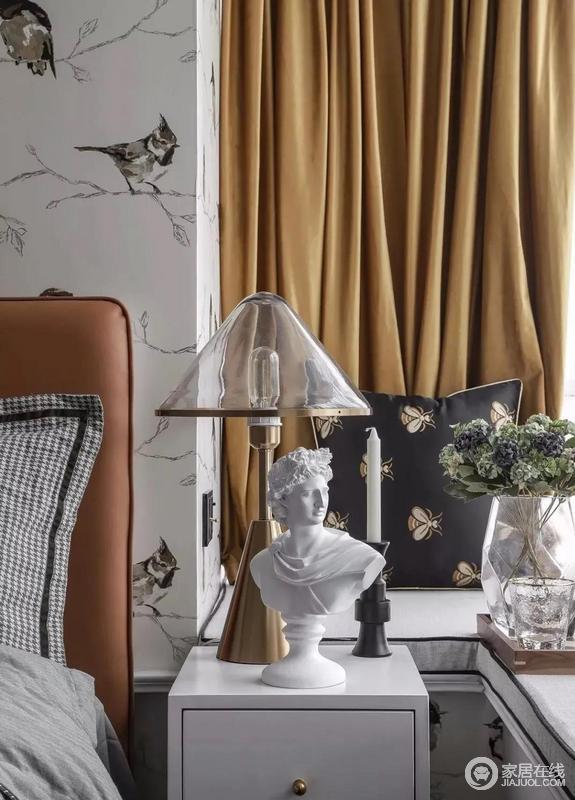 虽然空间有限,却十分温馨有韵味,床背与窗帘选用橙色与鹅黄搭配,色彩层次之间,造就复古时尚;床头柜上的石雕艺术品和玻璃台灯、精致小巧的软装摆件赋予生活更多风趣。