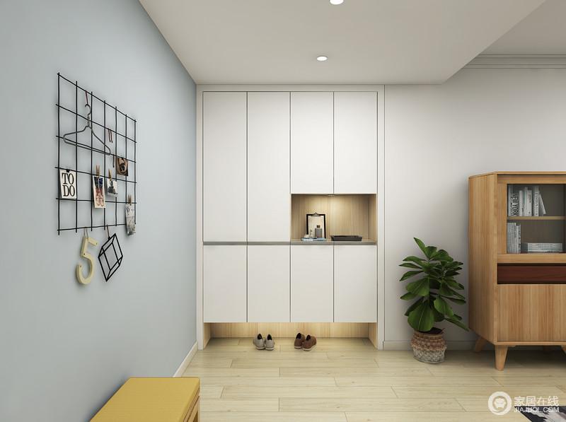 门厅以浅蓝色漆墙营造清幽,让主人回到家可以感受到放松,白色鞋柜嵌入墙面,丝毫不影响空间感,尽显实用和大气,蓝白调之间平衡出一种雅静;格子收纳架和条凳,让更换衣物也更为舒适。