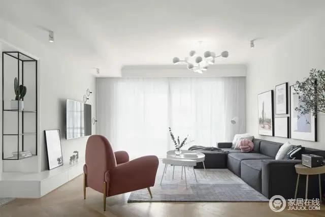 客厅以简约洁净的空间,布置上灰色的布艺沙发,白色双拼托盘茶几、还有一张暗粉色的休闲沙发椅,整体客厅空间充满现代极简的舒适与文艺气息。