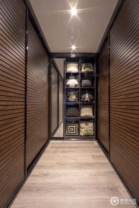 衣帽间并没有做成开放式设计,而是以褐色胡桃木条纹推拉门门将区域独立起来,让空间愈加规整;原木地板的朴质和几何置物格的简单,让收纳更为利落。