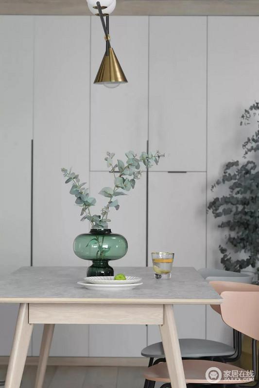 餐桌上的花瓶与果盘、水杯,结合铜色的吊灯,呈现出一个轻奢自然的用餐氛围感;墙面定制的收纳柜解决了实用性问题,裹挟着绿植,为空间带来生机感。