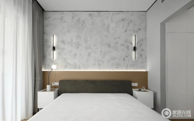 主卧的背墙用了简单的水泥艺术漆,搭配素色的床品和布艺窗帘,给人以安适的休憩氛围;房间的光线,白天,来自于大幅落地窗额自然采光,夜晚,则来自于两侧的壁灯,取代了卧室吊灯的压迫感,有助于营造柔和安然的睡眠环境。