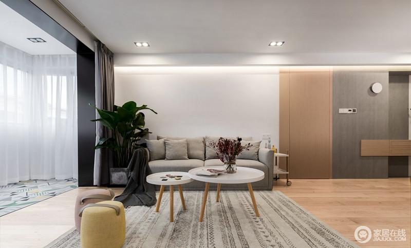 客厅是最能让人放松的地方,进入房屋的那一刻,便能在客厅里放飞自我,沙发前的圆形原木腿茶几,造型简约,可以放置零茶水点心及其他,桌面是凹型设计,能有效的放置物品下落;桌上的干花为整个简约风格的客厅增添了一抹彩色,两个彩色小布墩,可以当成是沙发的替补,要是在沙发上躺累了便来坐一会,让自己的颈椎也换个姿势。