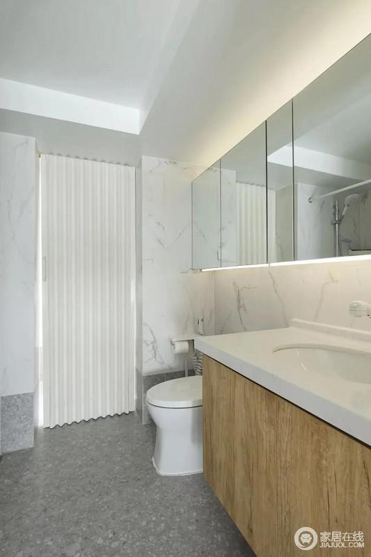 卫生间在灰色水磨石地砖基础,结合雅白的墙面砖显得十分干净;而洗手盆上方的镜柜延伸到马桶上方,并在吊柜上方暗藏了灯带,让空间显得温馨而又自然。