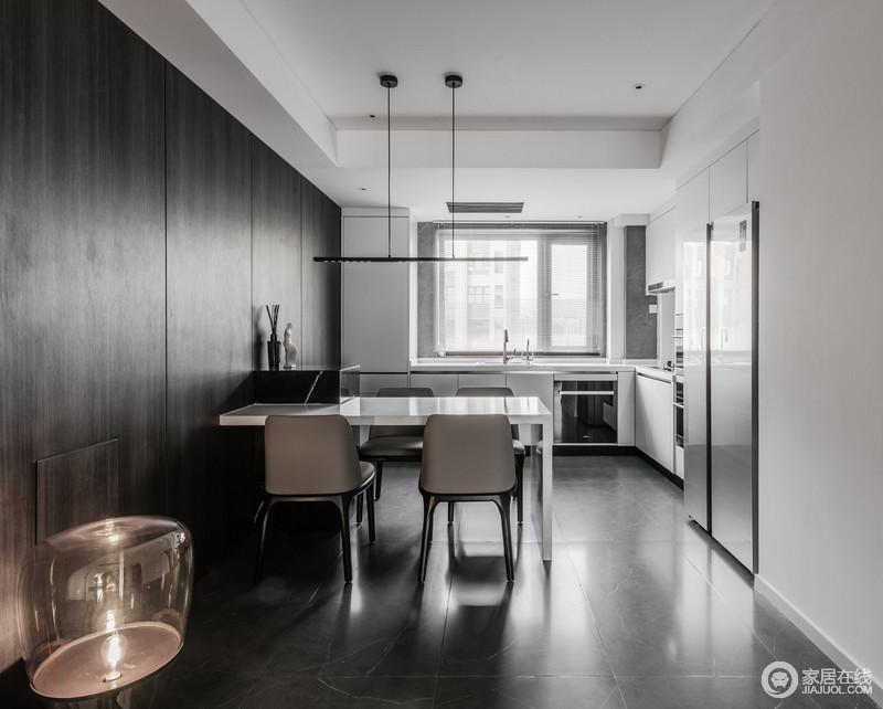 开放式厨房的餐桌和吧台构成一个水平线,增加了空间的储存空间;黑色板材的墙面搭配灰色砖石,与白色橱柜形成简约与经典之美。