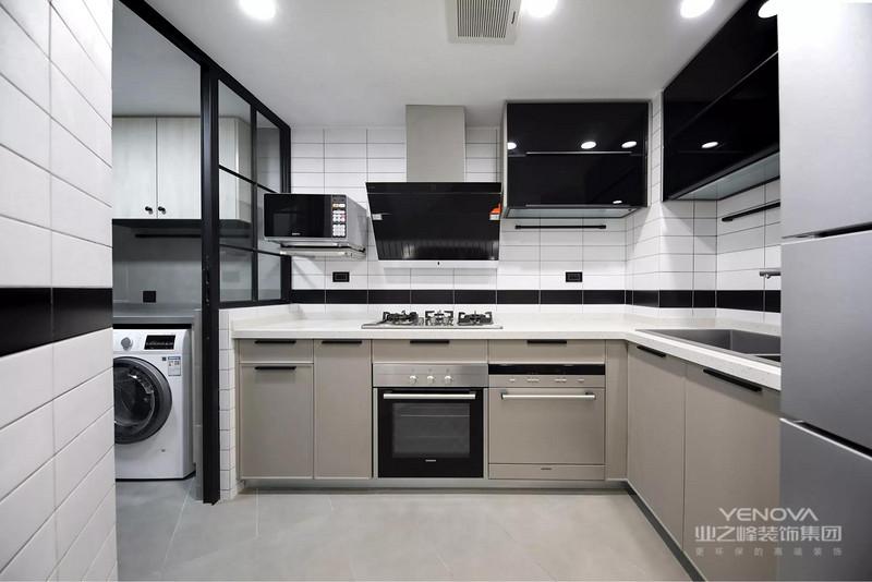 进门的右手边是厨房。家电一律是嵌入式安装,上吊收纳柜采用底面灯箱板。
