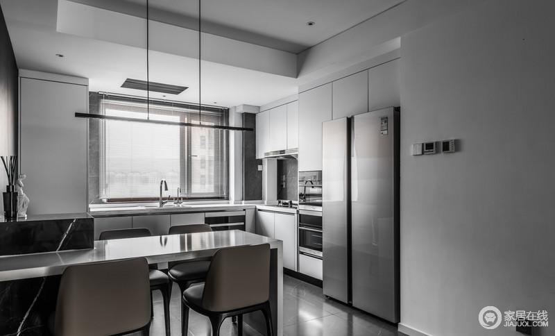 双开门的冰箱可以实现大量食材的长期储藏,与橱柜内嵌入的电器,突出了生活的质感;吧台简单地与餐厅做了分隔,却不失互动性,以黑白时尚,构成生活的美学。