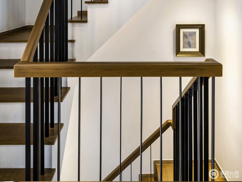 楼梯起到连接两个空间的作用,白墙的纯净与黑色铁艺栏杆的工业气息,构成黑白时尚,简单中给予对比的艺术,实木扶手与木框的挂画呼应着成就温馨。