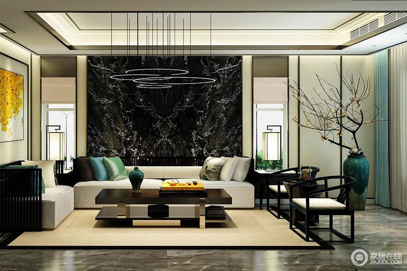 客厅的背景墙以黑色大理作装饰,与地板呈同色系的庄重大气,简约的云状吊灯既起到照明作用,又营造了空间反差艺术,而新中式落地灯对称的光晕,尽显温和;现代沙发因为靠垫、驼色地毯点缀,不显沉闷,两把圈椅的东方之魂,与花器、家具裹挟出了雅致。