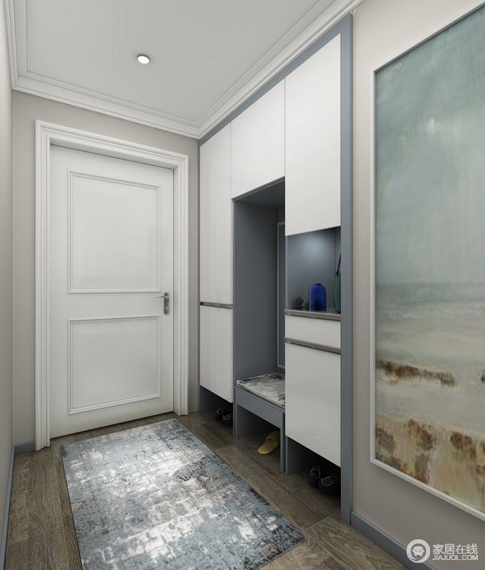 门厅以驼色为底色,搭配黑灰木地板,中性沉稳之中,奠定了空间的素静;设计师通过定制得蓝白鞋柜,以嵌入式的设计将空间的功能性发挥出来,更具收纳性,一副海滩挂画与地毯组合,调和着空间的色调,简而利落。