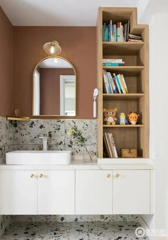 卫生间干区与次卧之间采用S墙设计,水磨石瓷砖搭配脏粉色背景,右侧设计置物架,可随手放置一些常用的小物。