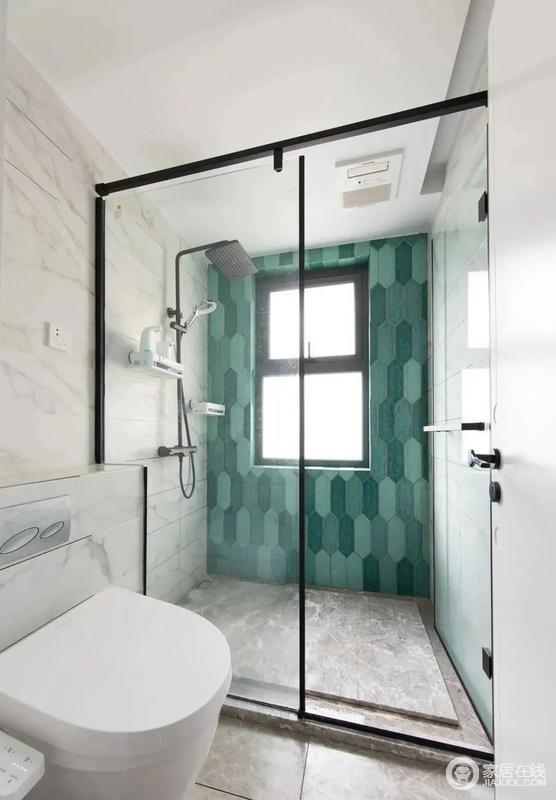 卫生间内部采用细框玻璃门隔断淋浴区,背景竖贴不同深浅的绿色六边砖,整体干净清新。