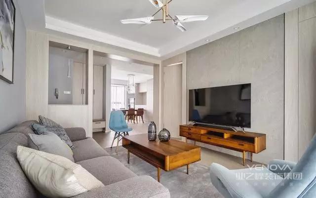 客厅光线透过黄色的窗帘,温暖了略冷的基调,由着木色元素贯穿全局。