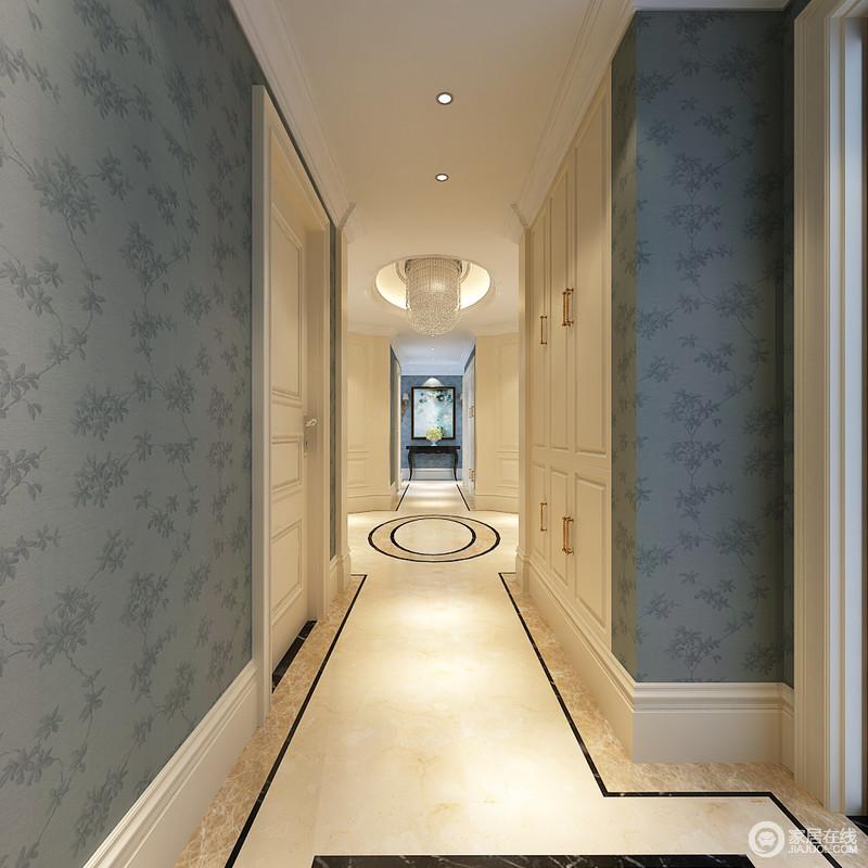 走廊比较深邃悠长,端景呼应了墙面上装饰的蓝底印花壁纸,内置的储物柜与居室门框则采用简白色调,中央地板拼花与天花吊灯造型上下相得益彰。