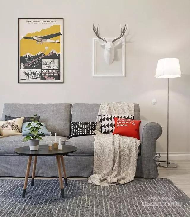 简简单单的灰色布艺沙发和地毯,搭配一个迷你的茶几和挂画、绿植、鹿角装饰等,客厅从软装细节处展现出了北欧风独特的美感。
