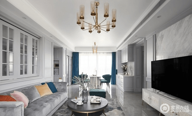 客厅主基调素雅,用恰到好处的软装提亮整体的明亮度,丰富视觉层次;黄铜元素、大理石背景墙、与家具互相协调,呈现大气却饱含精致韵味;沙发背景墙摒弃传统墙面,开了个折叠窗,让客厅与书房二者相通,增加两个空间的流动性和互动性,而灰色古典沙发搭配现代茶几,演绎新古典时尚。