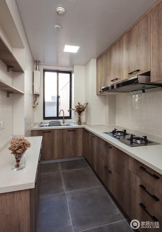 厨房的墙上以白瓷砖贴成了平整感,与木色橱柜形成了生动的反差,黑色的长条形把手让空间显得比较方正,利落而实用,让生活十分温情。