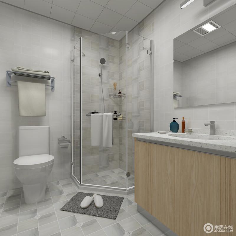 卫生间浅灰色的砖石铺贴在墙面,为了减缓空间的单调,以灰色晕染地砖来凸显艺术感;角落的淋浴室解决了私密性和干湿问题,搭配木纹盥洗柜和毛巾架,让生活更简单、舒适。
