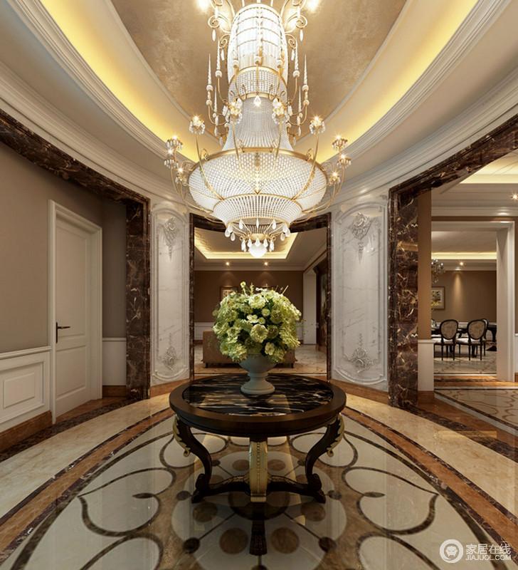 门厅内椭圆形的吊顶以金箔材质与灯带营造豪华,并与地面欧式拼花的椭圆造型呼应出对称的几何美学和大气;水晶灯的璀璨光照耀着整个空间,复古华丽和盘托出。