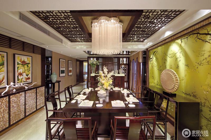 餐厅借中式窗棂的设计将吊顶打造出了空灵感,水晶吊灯平衡着挑高,与中式实木家具呈色彩上的呼应,格外大气;黄色玻璃板的墙面给空间增加了色彩感,与明艳生动的花卉挂画令空间盎然,而线条流畅地边柜以不同的造型和材质,给家和谐感;吧台通过木楞隔断和几何实木酒柜自成格局,让生活尤为精致。
