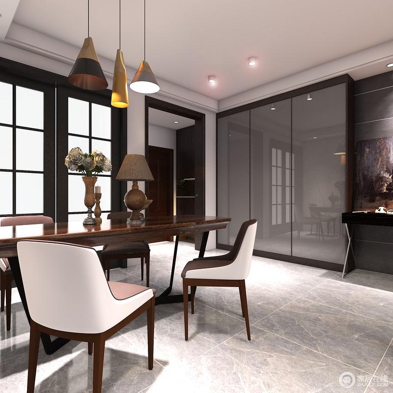 实木皮质拼接的座椅,无形中提升了整个空间的时尚感,让餐厅的就餐氛围简约高雅;餐桌上的高脚摆件与吊灯辉映,映衬在灰色镜面置物柜面里,彰显出轻奢精致的气场与格调。