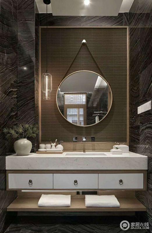 卫生间的结构设计得十分简单,黑灰色的大理石砖铺贴墙面,造就了硬朗和冷静,带着肌理之美,让空间极富质感;木框上悬挂得圆镜,搭配白色大理石台面,让卫浴生活也更为讲究。
