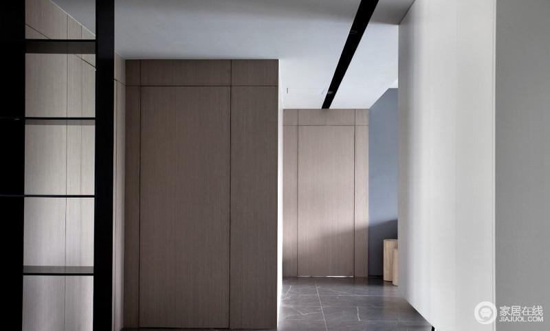 """廊道的概念很弱,于是我们用一段宽10cm、深10cm的黑色带状凹槽贯穿整个过廊,""""条带""""隐藏了区域内所有的照明筒灯、新风风口、空调回风口,使得整个顶面干净整洁且富有线条感,再搭配原木柜面,构成空间的自然朴质。"""
