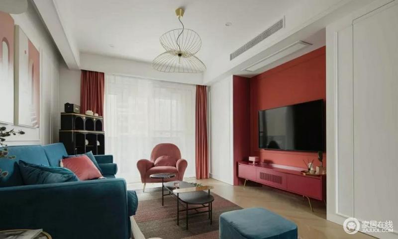 客厅由红粉色、蓝色两色为主基调,强烈的色彩碰撞,令空间充斥着年轻时尚感;丝绒、金属等轻奢材质的运用,让空间显得精致起来;个性的黑色几何储物柜搭配茶几,给空间带来稳重感,调和出色彩美学。
