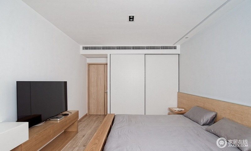 卧室简洁淡雅,强化复合地板通铺让自然的纹理和槽线将美学和精致感雕刻在空间;卧室没有主灯,却在床头做了灯带,加上顶面两边的筒灯,没有破坏空间的简单;白色衣柜与灰色床品调和出素静和大气,不抢眼又温和。