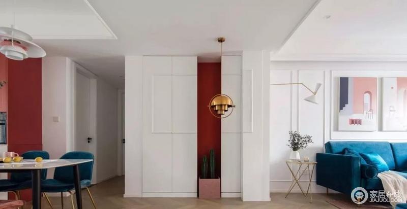 客餐厅开放式的格局增强了空间感,以顶部的梁和定制柜进行自然分隔。门厅以白色嵌入式储物柜的形式实现功能性;红色墙若隐若现,与绿植和黄铜处于同一平面,共造色彩与美学。