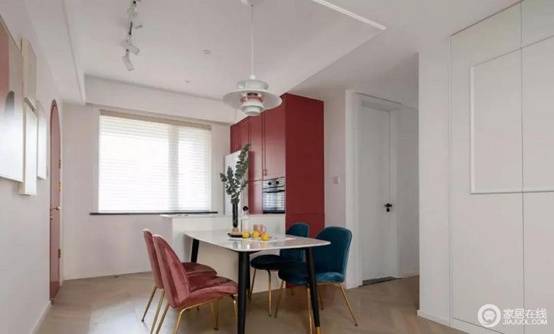 餐厅的色彩与客厅保持一致,白色的空间更显洁净,一排红色定制橱柜给予空间摩登感;橱柜内将冰箱、烤箱等电器嵌入其中,释放了厨房空间,也显得格外现代化;北欧风的餐椅,以桃红与宝石蓝撞色的形式为空间增色不少,白色灯笼造型的吊灯点缀出艺术感。