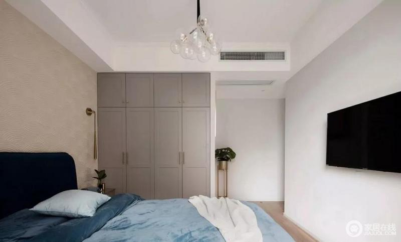 次卧空间相对简单一些,大面积墙面作了刷白,背景墙铺贴了米色的墙纸,以简单的纹理突出设计感;灰色定制衣柜与蓝色床品,在对比之中,营造出优雅宁静,而黄铜质感的灯具和花架,无疑,给空间注入一种精致。