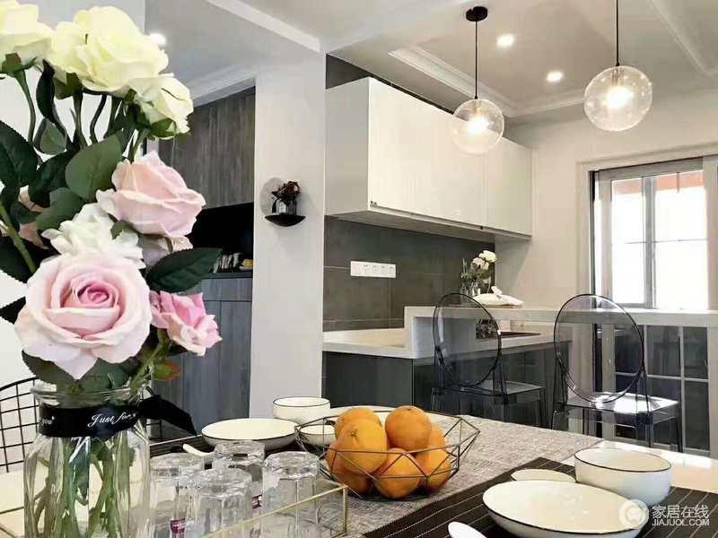 厨房以灰色砖铺贴墙面,橱柜的白色与灰色搭配出简约感,格外实用;玻璃球泡灯搭配透明的塑料椅子,让吧台区也满是设计感。