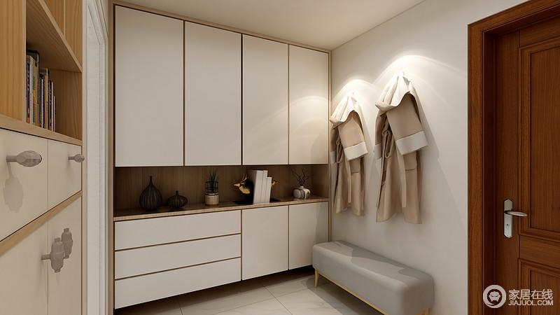 门厅的设计本着利落和实用的主张,将白色定制得储物柜做成整面式设计,强调储物;白色的设计也提亮了空间,灰色床尾凳搭配衣钩,让入户也很是贴心。