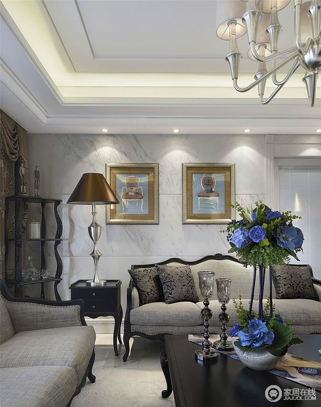 客厅的角落丝毫没有被忽视,设计师将曲线感地实木酒架填补空洞,并合理地提升了生活的品质;整体灰色调墙面和沙发,因为黑色欧式茶几和金色画框地组合,凸显出一种复古的华丽。