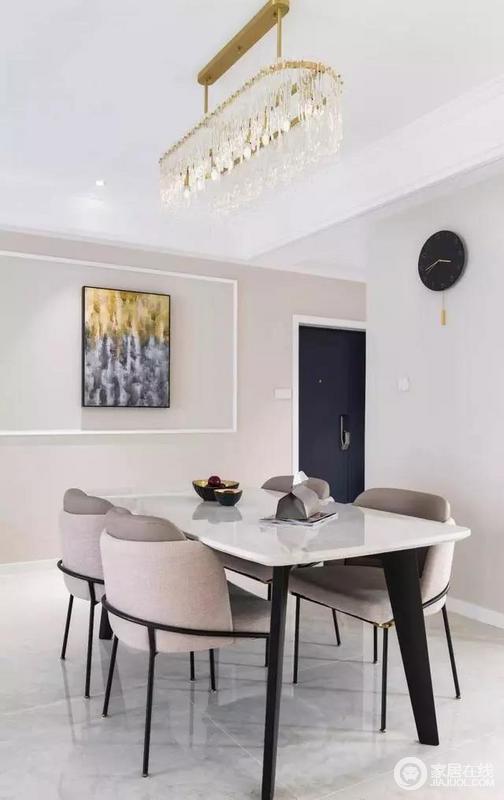 墙面渐变色的装饰画与原本的立面形成一种层次感,一旁的黑色挂钟与餐桌黑色的餐桌椅底座为空间融入了经典之色,与餐椅的暖灰色衬托起舒适、敦实。
