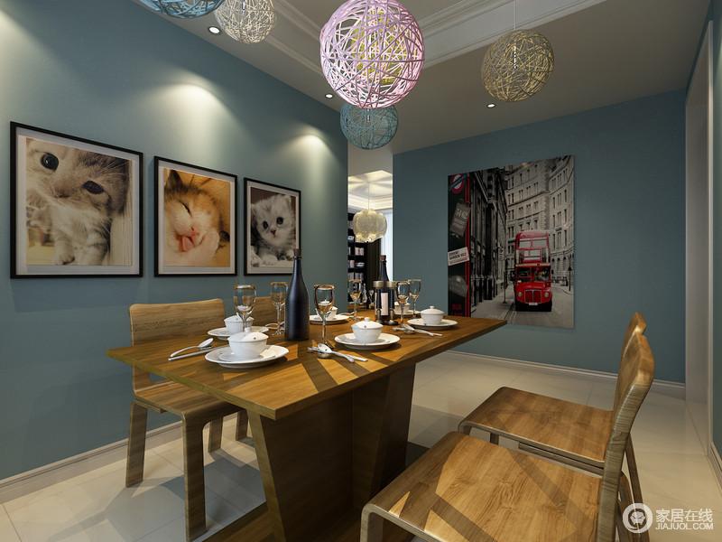餐厅结构规整有序,蓝色调的墙面显得宁静了不少,可爱的猫咪照片带着爱心,让空间升温;彩色铁艺吊灯的镂空感显出工业简洁,与实木餐桌餐椅的厚实对比出材质的迥异,却让空间缤纷温和。