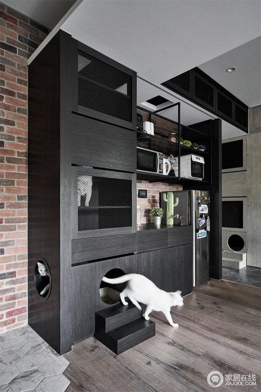 空间没有用压抑地灰色和黑色,而是用了红砖的壁纸做过渡,让人一进门就感受到工业的气息,黑色橱柜的结几何设计与实用之能,让空间格外利落。