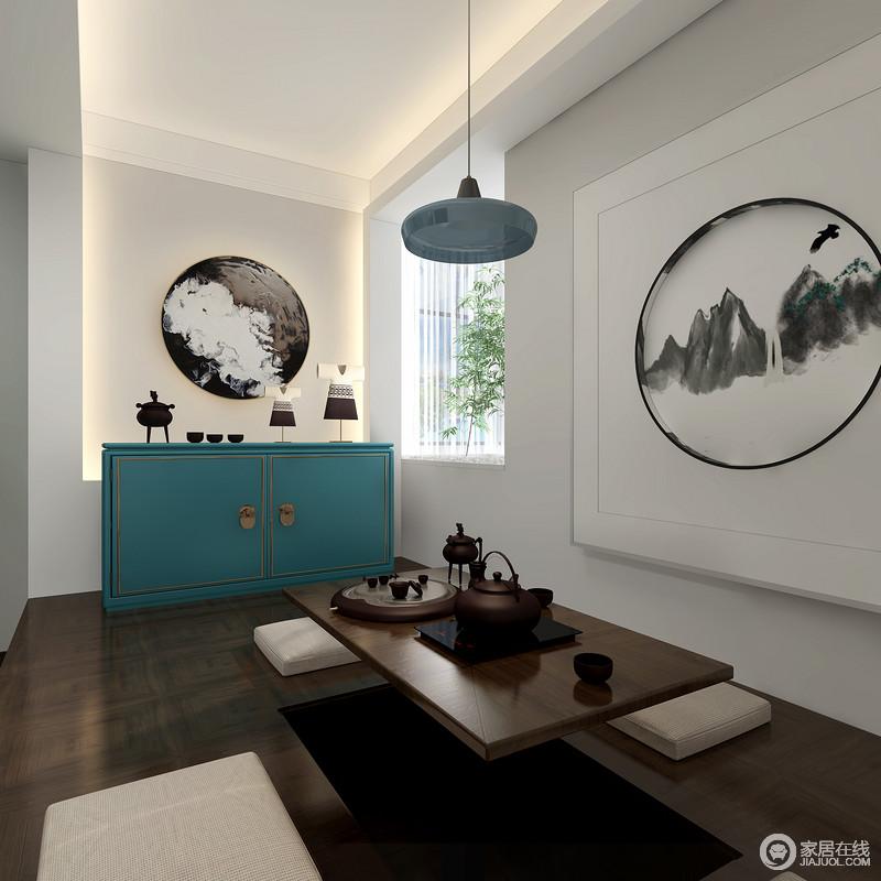 茶室整体结构简洁,以中式写意画来突出空间的墨意妙趣,蓝色边柜和吊灯为这个中式的空间生发新味;而实木茶几与座椅因为茶器的考究,赋予生活温实与精致。
