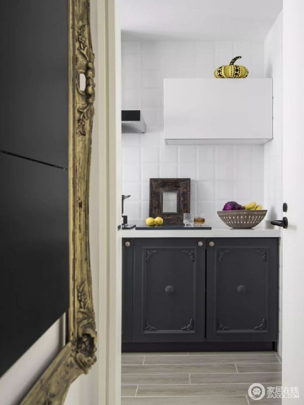开放式的空间自带一种空间感,从走廊边可以看到黑白之色的厨房,带来现代之气,简单利落,却充满生活气息,水果盘和餐具,满是日常的温馨。