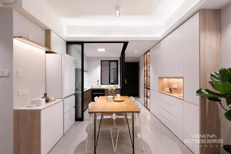 走过玄关就到了餐厨合一的空间,餐厅侧方的餐边柜一直延伸到了玄关处,另一侧也做了矮柜的设计,冰箱放在角落里,整个空间看起来宽敞又明亮。