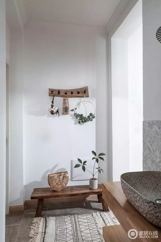 玄关仅保留一个换鞋凳,原始的树枝板材拼接的挂钩,挂上小饰品,灰色地砖上垫上一块地毯,整个空间显得简洁而又自然,有种户外的生机感。