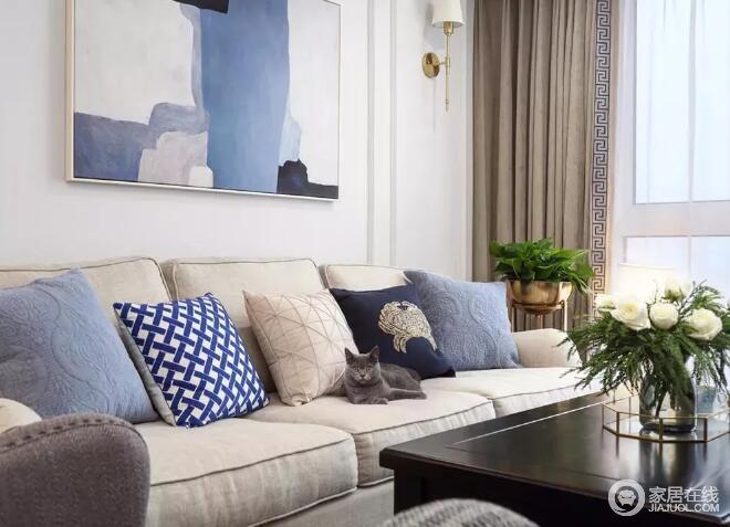 舒适的米白色布艺沙发,布置上素雅的蓝色抱枕,沙发墙再挂一幅抽象的黑白蓝装饰画,舒适优雅。